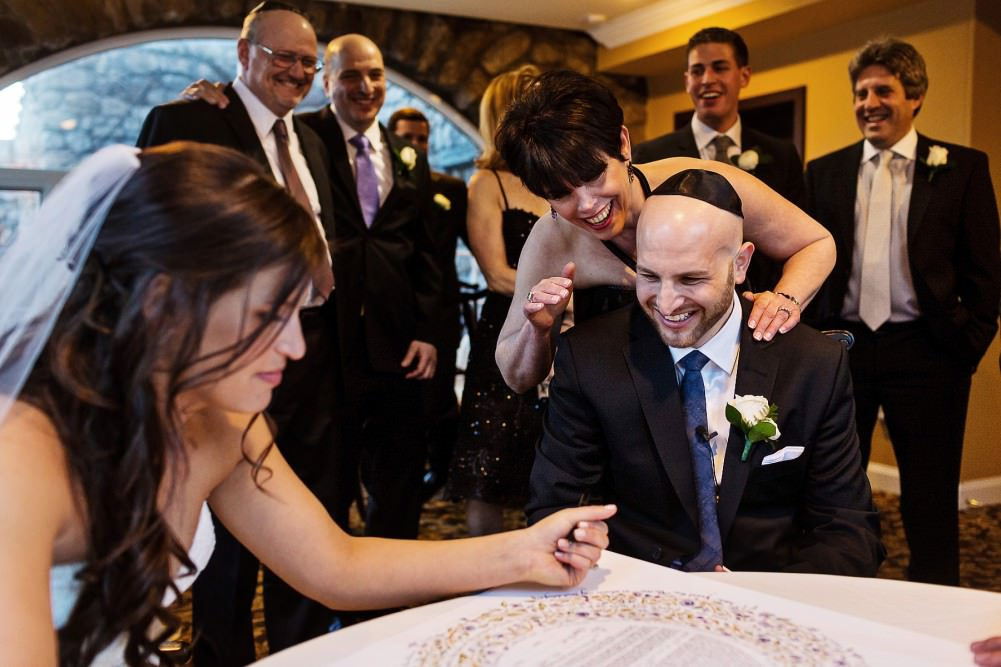 a happy jewish wedding, signing the ketubah
